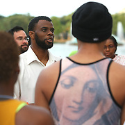 """DeQuan Shanks (center) leads the crowd in speech at Lake Eola park during the """"National Moment of Silence"""" event at the Lake Eola bandshell in downtown Orlando, Florida on Thursday, August 14, 2014. In light of the recent killing of eighteen year old Mike Brown in Ferguson, Missouri, citizens across America are gathering in solidarity to hold vigils and observe a moment of silence to honor victims of suspected police brutality. (AP Photo/Alex Menendez)"""