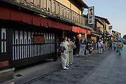 Tourists dressed in traditional kimono stop for a selfie outside a Japanese restaurant in the Gion district of Kyoto.