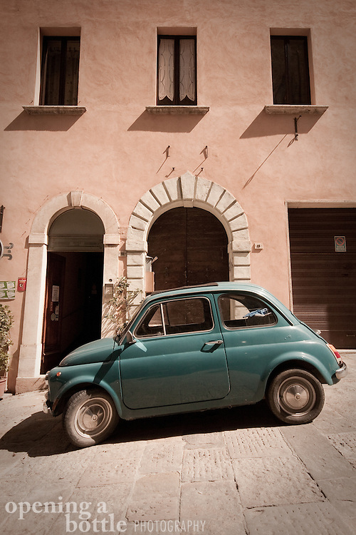 An old Fiat 500 is parked on a hill in Montepulciano, Siena, Tuscany, Italy.