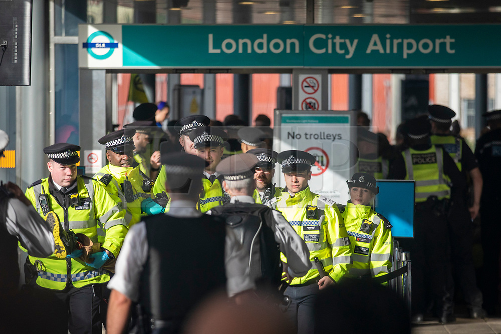 © Licensed to London News Pictures. 10/10/2019. London, UK. Police arrest an Extinction Rebellion protester at the DLR entrance to London City Airport. Protesters planned to occupy the terminal building in a 'Hong Kong-style' shutdown as part of ongoing protests calling on government departments to tackle the Climate Emergency. Photo credit: Rob Pinney/LNP