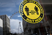A yellow and black sticker which urges social distancing to customers, faces the street from inside a closed retailer's window in Waterloo, where the London Eye still revolves while empty during the third lockdown of the Coronavirus pandemic, on 11th March 2021, in London, England.