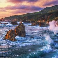 Crashing waves, sea stacks, and low marine clouds at sunset along the Big Sur Coast, California.