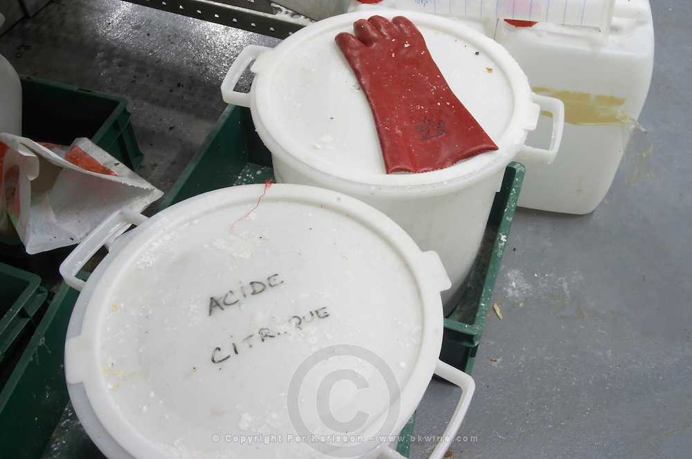 Plastic bucket with Acide Citrique, Citric Acid, C6H8O7, frequently used in wine production. Citrus. With a rubber glove. Mas La Chevaliere. near Beziers. Languedoc. France. Europe.
