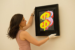 © London News Pictures. 26/06/15. London, UK. A Bonham's employee hangs up Andy Warhol's 1982 'Dollar Sign', which is part of Bonhams Contemporary Art Sale, New Bond Street, Central London. Photo credit: Laura Lean/LNP