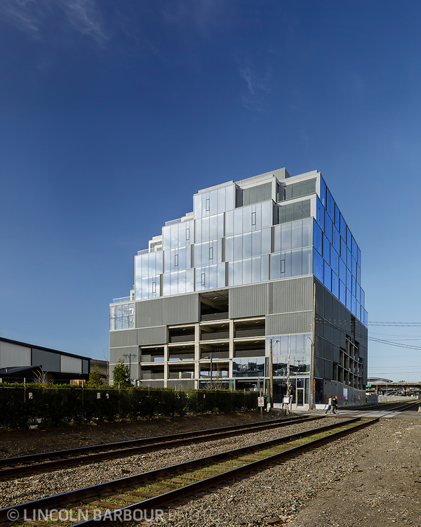 The new 7 Stark Building stands over the railroad tracks in the industrial east side of Portland, Oregon.