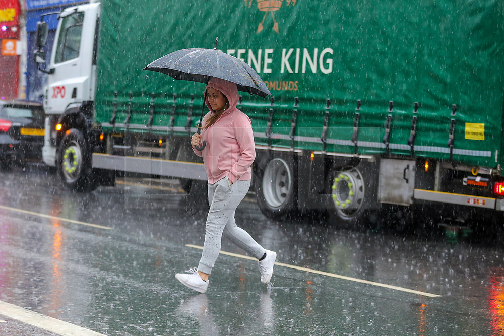 © Licensed to London News Pictures. 18/06/2021. London, UK. A woman shelters from the rain underneath an umbrella crossing a road in north London, as wet weather conditions continue after a warm dry spell. Photo credit: Dinendra Haria/LNP