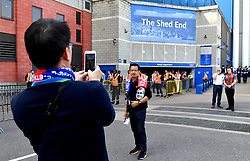 A fan has their picture taken wearing a commemorative scarf of the match before the Premier League match at Stamford Bridge, London.