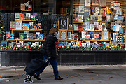 A shopper walks past Christmas books stock in the window of a closed Chelsea branch of Waterstones on the King's Road during the second Coronavirus lockdow when most non-essential retailers and small businesses remain closed by order of the government, on 13th November 2020, in London, England.
