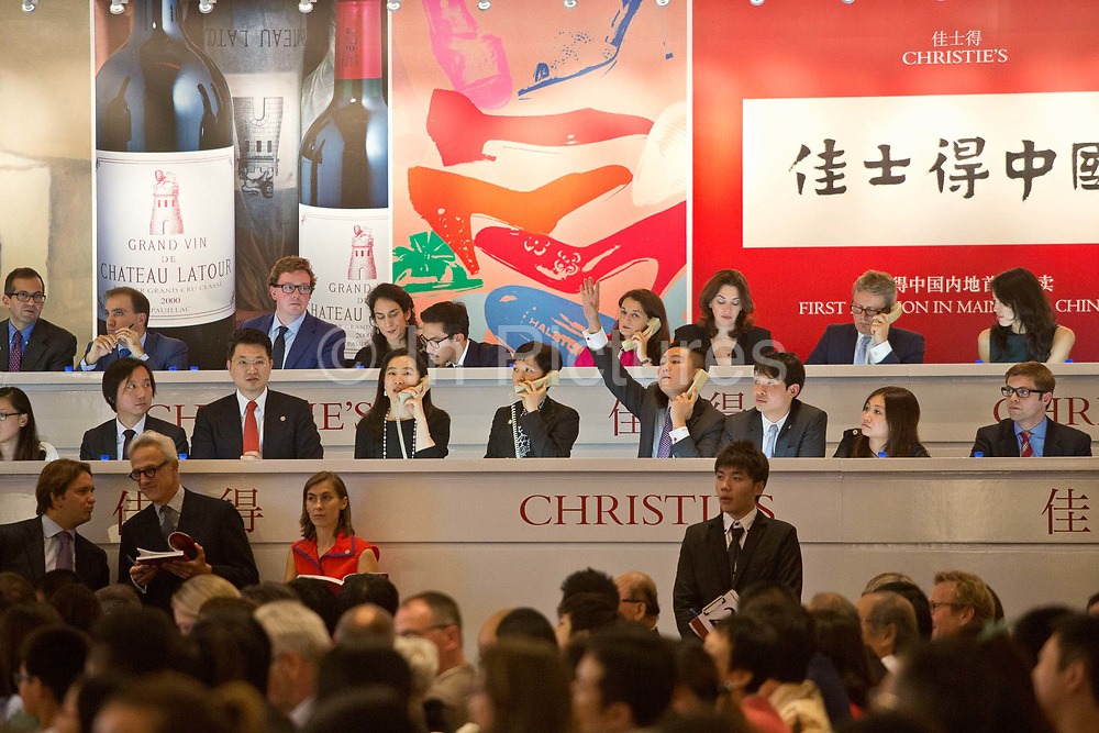 """Staff members man the phone lines for overseas clients during Christie's very first mainland China auction in Shanghai, China September 27,  2013. Both Southeby's and Christie's have opened an office in Mainland China in the past year, however they face overwhelming odds as China's state-owned auction houses such as Poly and Jiamu enjoys a near monopoly over China's art procurement market as foreigners are not allowed to buy vaguely defined """"historical"""" art."""