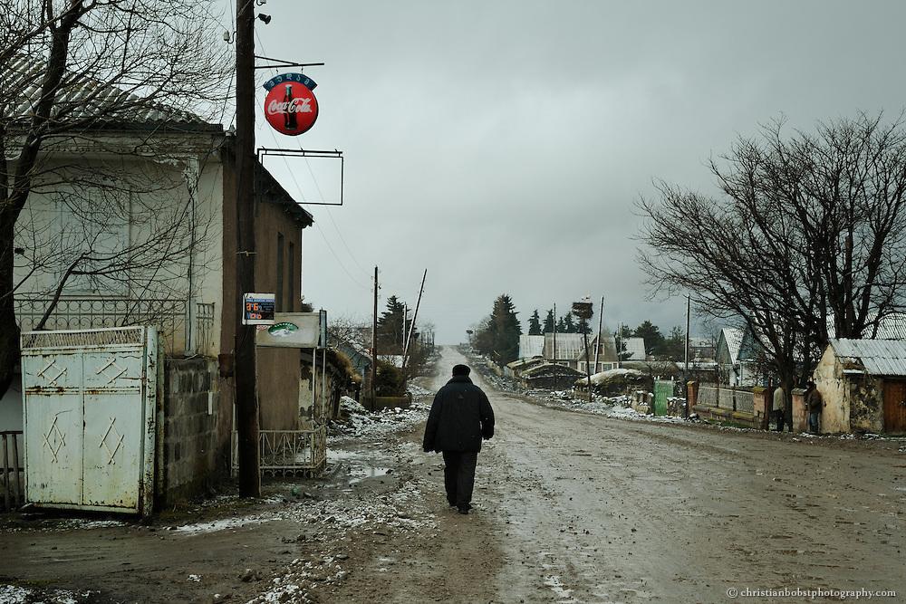 A man walks down the main street of Gorelovka.