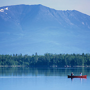 Couple in a red canoe paddling through Nesowadnehunk Deadwater on the Penobscot River with a view of Mount Katahdin in the background.