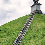 A group of tourists climb the steps at the Lion's Mound (Butte du Lion), an artificial hill built on the battlefield of Waterloo to commemorate the location where William II of the Netherlands was injured during the battle. The hill is situated on a spot along the line where the Allied army under the Duke of Wellington's command took up positions during the Battle of Waterloo.