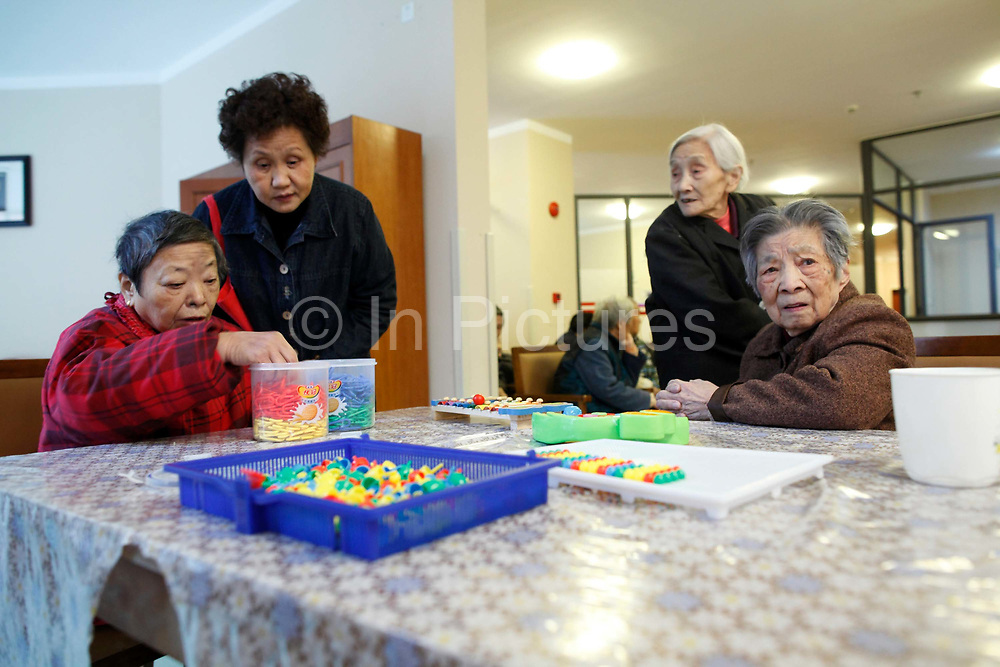 Elderly women who all suffers from Alzheimer's and dementia, sit in the recreation room at the Shanghai 3rd Welfare House in Shanghai, China on 28 November 2010.  Dementia and Alzheimer's is fast establishing themselves as a major health risk for China's booming elderly population, placing strain on families and society a like, especially in major cities such as Shanghai, where the traditional system of large family and caring for the old by family members give way to small family units and retirement homes.