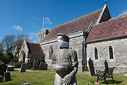 Covid 19 - mask placed on statue of a stonemason in St Georges' churchyard, Langton Matravers, Dorset during Coronavirus lockdown. UK April 2020