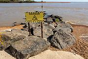 Danger Keep off Rocks sign on rock armour groyne, mouth of River Deben at Felixstowe Ferry, Suffolk, England, UK