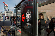 A young woman reads bus routes inside a bus stop shelter on London Bridge, on 19th April, in the City of London, England.