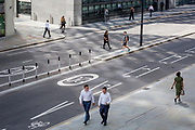 Pedestrians cross London Wall, the site of the original Roman walled boundary of their Londinium settlement - now known as the City of London, the capital's financial district, on 21st August 2018, in London, England.