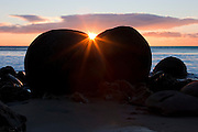The rising sun shines between two of the Moeraki Boulders, located at Koekohe Beach along Otago coast of New Zealand. Dozens of large, almost perfectly spherical boulders line the beach. About two-thirds of the rocks range in size from 1.5 to 2.2 metres (4.6 to 6.7 ft).