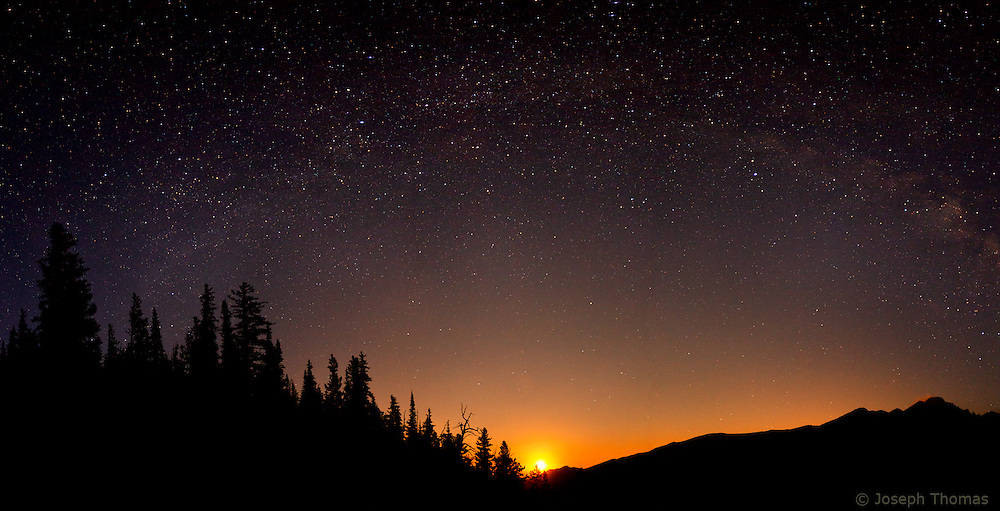 The radiant disc of the moon crests the horizon at Glacier Gorge with the dome of the Milky Way arcing above.