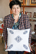 Mirjana Palija holds a cushion decorated with Zmijanje embroidery in the small gallery/souvenir shop of the 'Duga' Humanitarian Women's Association (Humanitarno udruzenje zena 'Duga'), Banja Luka, Bosnia and Herzegovina (14 April 2014). Zmijanje embroidery (Zmijanski vez) is a distinctive style of embroidery unique to this region of Bosnia and Herzegovina, and is due to be inscribed on the UNESCO list of Intangible Cultural Heritage in October 2014. © Rudolf Abraham