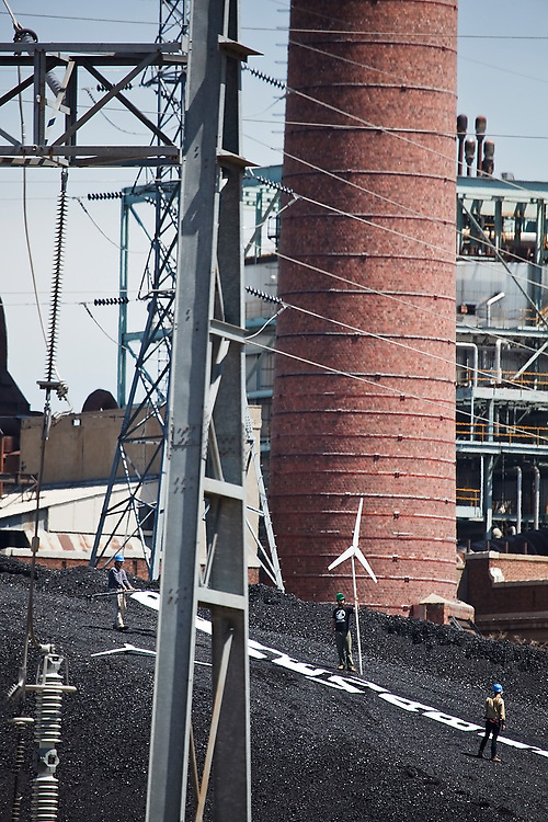 """Kate Clark (r-l),  Eric Ross, Erik Bonnett and Tom Weiss (not shown) stage a protest with mock wind turbines and a giant """"Renewables Now"""" banner on the coal pile at the Valmont Power Plant in Boulder, Colorado on April 27, 2010. The four climate activists claimed the coal mound for over an hour before they were arrested for trespass."""