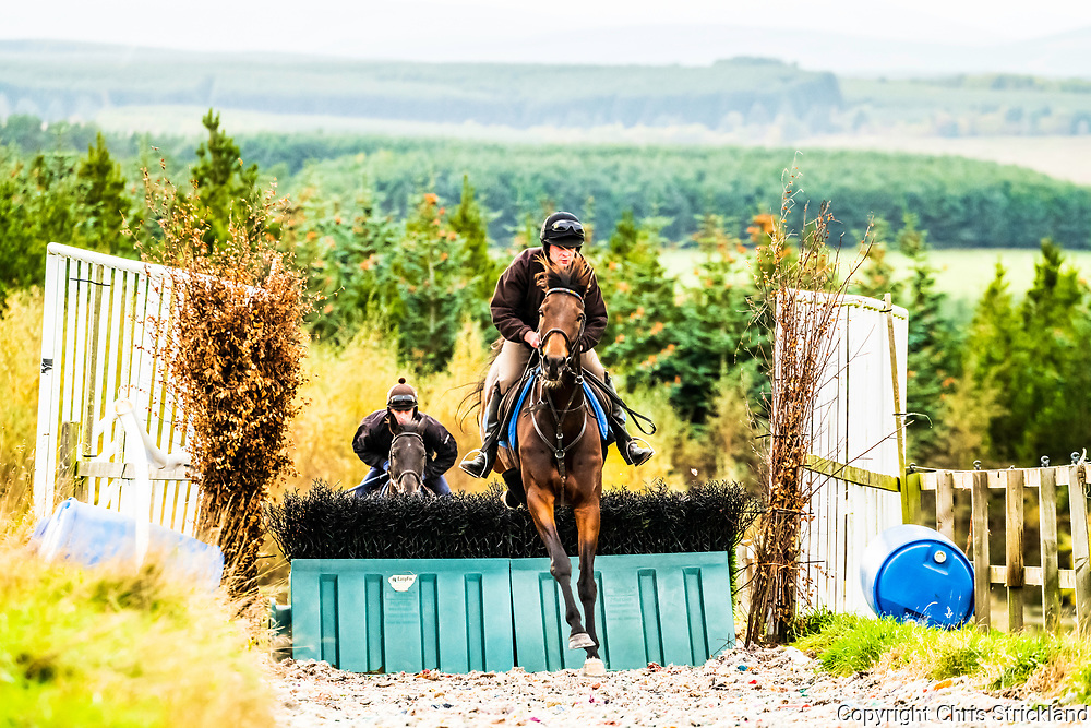 Camptown, Jedburgh, Scottish Borders, UK. 16th October 2018. National Hunt racehorse Scotswell, closely followed by stable mate Rhymers Stone, are schooled over fences at the yard of Harriet Graham.
