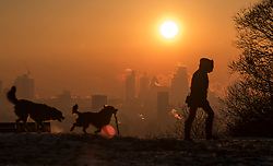 © Licensed to London News Pictures. 12/12/2017. London, UK. A dog walker at sun rise on Hampstead Heath in north London as the sun rises over the city of London on a freezing morning. Temperatures across the the UK dipped overnight with some regions expected to drop to -13C (9F). Photo credit: Ben Cawthra/LNP