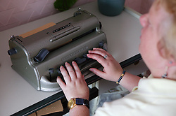 Partially sighted woman using brail machine,