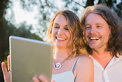 Close-up of couple laughing together while looking at tablet, Bavaria, Germany