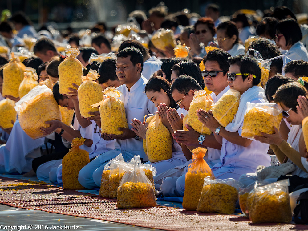 """02 JANUARY 2016 - KHLONG LUANG, PATHUM THANI, THAILAND: People hold marigolds and pray at Wat Phra Dhammakaya on the first day of the 5th annual Dhammachai Dhutanaga (a dhutanga is a """"wandering"""" and translated as pilgrimage). More than 1,300 monks are participating pilgrimage through central Thailand. The purpose of the pilgrimage is to pay homage to the Buddha, preserve Buddhist culture, welcome the new year, and """"develop virtuous Buddhist youth leaders."""" Wat Phra Dhammakaya is the largest Buddhist temple in Thailand and the center of the Dhammakaya movement, a Buddhist sect founded in the 1970s. The monks are using busses on some parts of the pilgrimage this year after complaints about traffic jams caused by the monks walking along main highways.          PHOTO BY JACK KURTZ"""