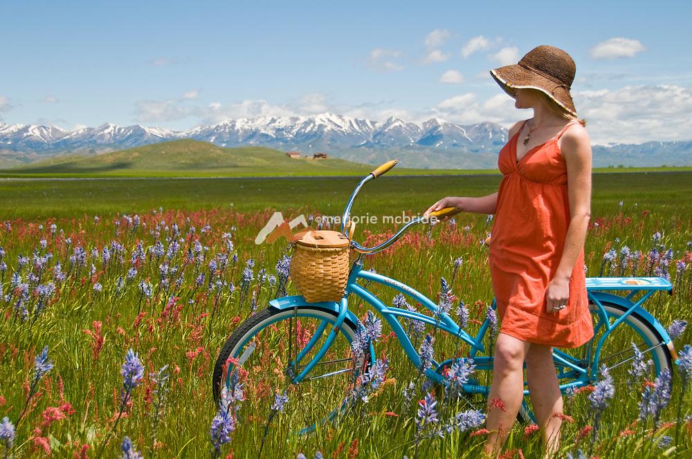 Woman in sun dress biking in a field of wildflowers during spring in Idaho.