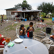 Abigail Cantu, left, 10, eats a sandwich with her siblings Sara, 14, Jeremias and Marcos, both 7, outside their home Nov. 29 near La Villa. Their father, Luis Cantu, raises the children on his own and does odd jobs to support them. <br /> Nathan Lambrecht/The Monitor
