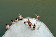 Nederland, Nijmegen, 25-62020 Een warme dag in de zomer . Mensen trekken naar de oevers van de waal en de spiegelwaal in het rivierpark aan de overkant van Nijmegen . Vanaf een van de peilers van de spoorbrug duiken jongeren in het water . De warmte, hoge temperatuur, drijft mensen naar het water . Het is verboden in de rivier te zwemmen vanwege de stroming en het drukke scheepvaartverkeer . Foto: ANP/ Hollandse Hoogte/ Flip Franssen