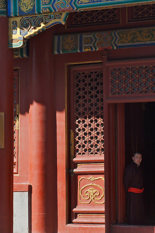 A monk stands inside the doorway of a hall at Yonghegong.  This Tibetan Temple is known to tourists as Lama Temple and it's located in Dongcheng District Beijing, China. This is the largest Temple of its kind outside of Tibet.  In 1723 the structure was turned into a Temple after the resident became the third Qing Emperor.