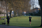 At the beginning of the second week of the UKs Coronavirus lockdown and in accordance with government guidelines for social distancing, family group isolation but local daily exercise, a runner and a walker practice sensible social distancing while enjoying late sunlight in Ruskin Park, a green public space in the borough of Lambeth, on 30th March 2020, in south London, England.