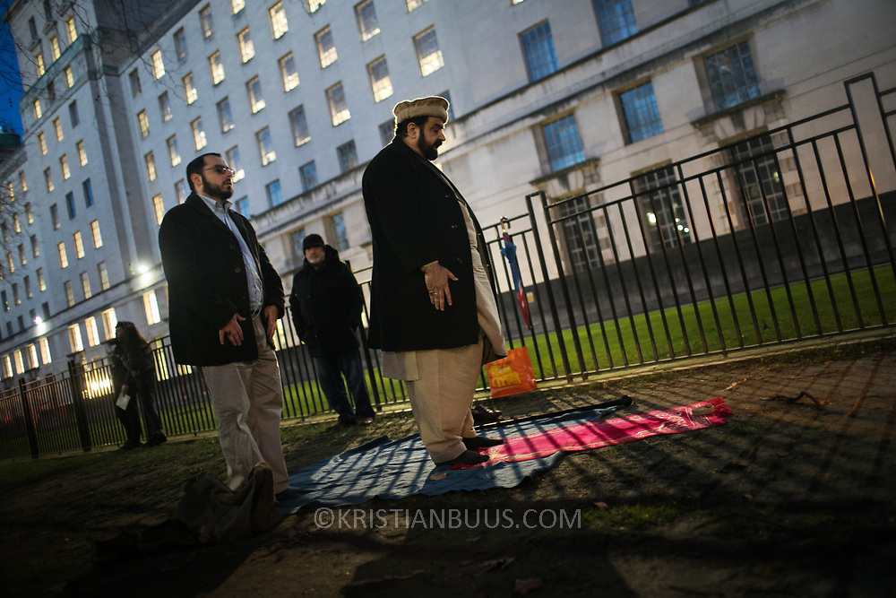 Protesters agains the visit by Saudi prince Bin Salman gather opposite Downing Street March 7th 2018 in London, United Kingdom. Two men pray. Many are angry at the Saudi involvement and continued bombing in Yemen with tens of thousands of civilian casualties and many more displaced by the war.