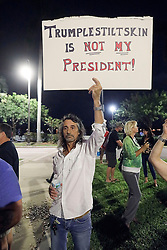 November 11, 2016 - Florida, U.S. - A man protests against the election of Donald Trump as the 45th President of the United States Friday, November 11, 2016 in front of the luxury condominium towers that bear his name along the waterfront in West Palm Beach, FL.  Damon Higgins / The Palm Beach Post (Credit Image: © Damon Higgins/The Palm Beach Post via ZUMA Wire)