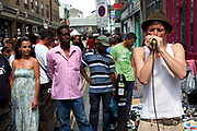 Harmonica player at Brick Lane Market. Official stalls selling clothers, food and all manner of crafts and junk make up the mainstay of the market though. These unofficial sellers though give the market it's unique atmosphere. This market is a weekly event in London's East End.