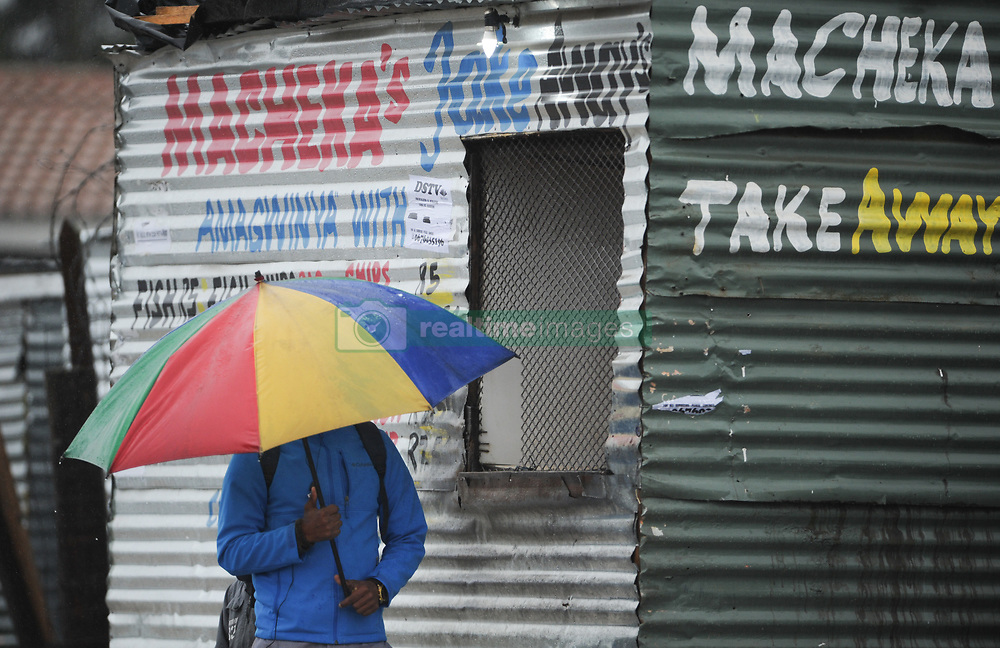South Africa - Cape Town - 09 July 2020 -  A man with a colourfull umbrella waits outside a shop in Wallacedene. A major cold front has made landfall in the Western Cape. Its expected to bring bitterly cold and wet weather, with strong to gale-force north-westerly winds of 60-74km/h and gusts up to 100km/h. The cold front is followed by another cold front and the Western Cape can expect to have cold weather until Sunday.  Picture: Henk Kruger/African News Agency(ANA)