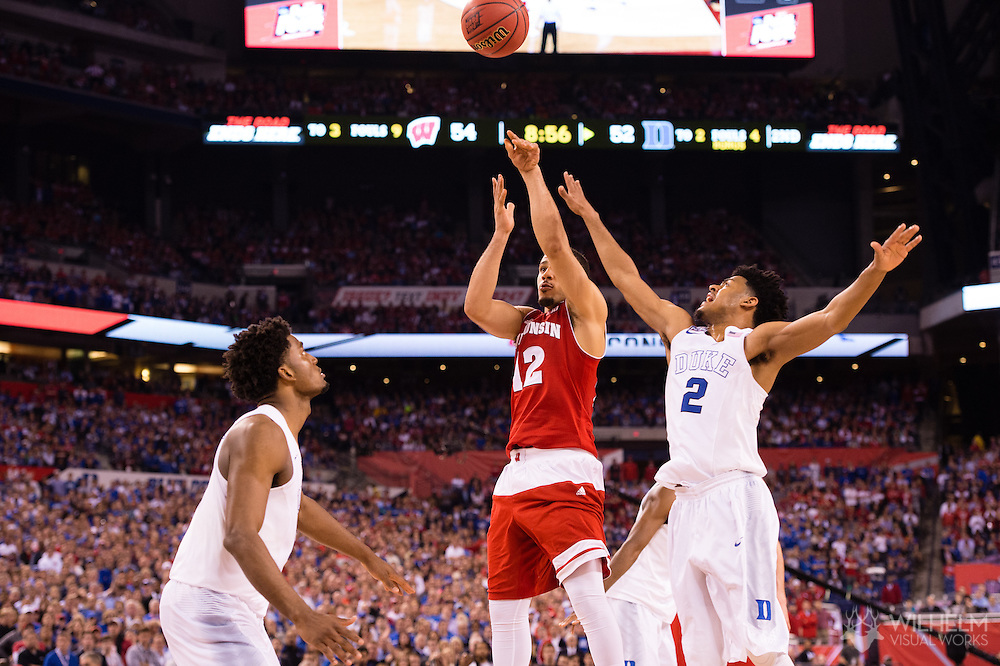 06 APR 2015:  Guard Traevon Jackson (12) of the University of Wisconsin shoots between Forward Justise Winslow (12) and Guard Quinn Cook (2) of Duke University during the championship game at the 2015 NCAA Men's DI Basketball Final Four in Indianapolis, IN. Duke defeated Wisconsin 68-63 to win the national title. Brett Wilhelm/NCAA Photos