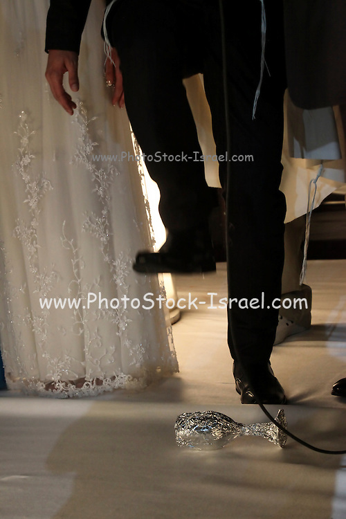 Traditional Jewish Wedding groom breaks glass as a sign for good luck and prosperity