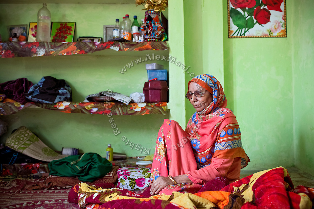 Kameeza Bee, 60, a widow 'gas-survivor' now suffering from cancer, is sitting on the floor of her home in Nawab, one of the water-affected colonies near the abandoned Union Carbide (now DOW Chemical) industrial complex in Bhopal, Madhya Pradesh, India. Kameeza and her family fed on contaminated underground water until 2010, when some pipeline was installed reached her home.