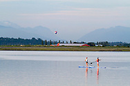 Two Stand Up Paddleboarders on the Nicomekl River near Crescent Beach in Surrey, British Columbia, Canada.