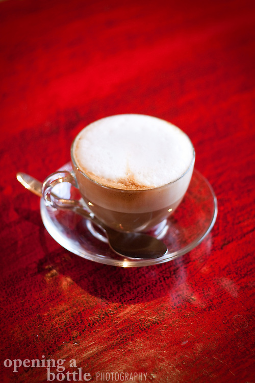 A cappuccino on a red table at a hotel-restaurant in Montepulciano, Tuscany, Italy. Traditional Italian coffee drink.