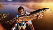 A young boy holds up a big fish he just caught on a lake while sitting in boat.