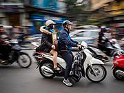 25 DECEMBER 2017 - HANOI, VIETNAM: People on a motorscooter navigate traffic in the Old Quarter of Hanoi.     PHOTO BY JACK KURTZ