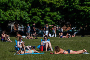 People enjoy the sun on Clapham Common after the Government eased restrictions and allowed people to meet - Lambeth Council have replaced signs to say stay alert and to allow people sit on benches. The eased 'lockdown' continues for the Coronavirus (Covid 19) outbreak in London.