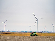 03 JANUARY 2020 - MONTEZUMA, IOWA: A farmer in his tractor in front of wind turbines in farm fields along US Highway 63 near Montezuma, Iowa. Iowa is a leader in wind energy and generates about 35% of its electrical needs through wind turbines.       PHOTO BY JACK KURTZ