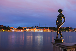 Bronze statue stands against a backdrop of Stockholm's Gamla Stan region of the city, Stockholm, Sweden