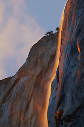 Light reflects off Horsetail Falls, formed by melting snow, in Yosemite National Park, making the water appear to be on fire.